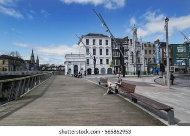 Cork, Ireland - April 14, 2015. People relax in a park at the quayside next to the Parade Street, at the city of Cork in southern Ireland.