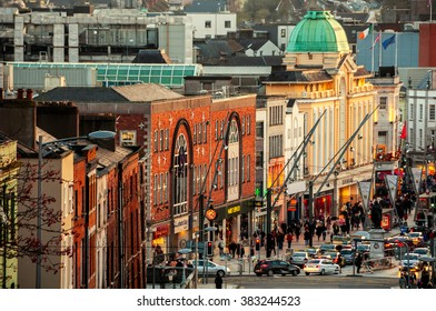 CORK, IRELAND - DECEMBER 7, 2014: City center with various shops, bars and restaurants. Car traffic and people at the street.
