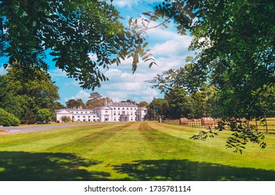 CORK, IRELAND - JULY 13 - Cork's famous Fota House in the distance with lawn and leaves in the foreground with unidentified people outside enjoying the sunshine July 13, 2013, Cork, Ireland.