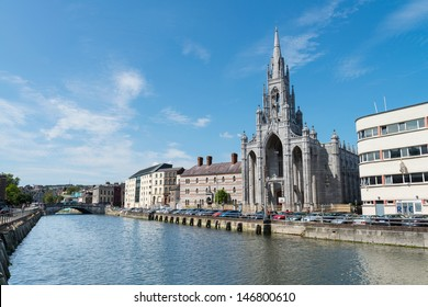 CORK, IRELAND - JULY 20 - The historic Holy Trinity Church which dates back to 1832 on Fr. Matthew Quay with unidentified pedestrians walking the River Lee, July 20, 2013, Cork, Ireland.