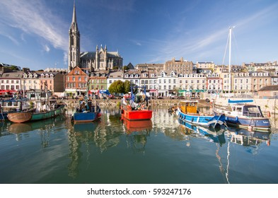 Cork, Ireland - September 15, 2016: The dominating form of St Colman's Cathedral rises above the terraced streets and colourful fishing boats of the small tourist city of Cobh on Cork Harbour.