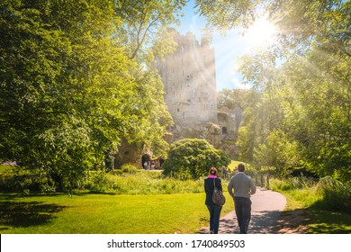 CORK, MUNSTER/IRELAND - JUNE 30 2013: Unidentified couple walking towards the historic Blarney Castle on a sunny day.