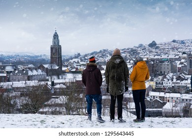 CORK, MUNSTER/IRELAND - MARCH 01 2018: Three people standing on a hill overlooking Shandon and St. Anne's Church in Cork City during a snowstorm.