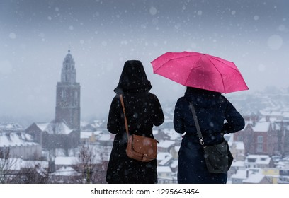 CORK, MUNSTER/IRELAND - MARCH 01 2018: Two people standing on a hill overlooking Shandon and St. Anne's Church in Cork City during a snowstorm.