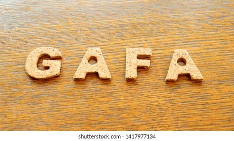 """Cork Text Block of """"GAFA"""" on wooden table"""