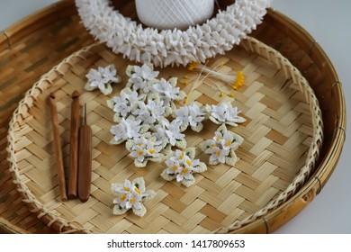 Cork tree flowers crochet and crown flowers crochet with wood crochet needles on basketry background. Thai crochet garland.