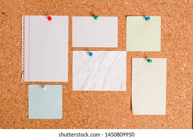 Corkboard with different color and size papers fixed by a pin. Rectangle and square shaped sheets stuck on a billboard by colored thumbtacks. Notice board with empty reminder note.