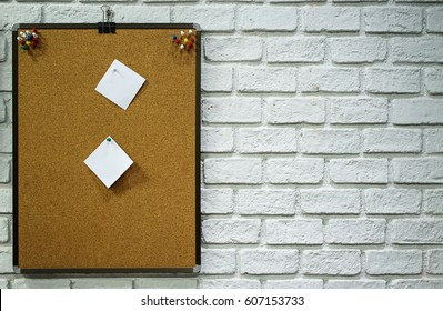 Corkboard with paper placed on white wall brick background