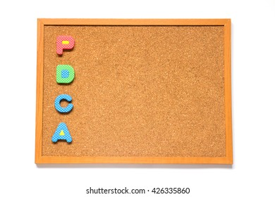 Corkboard with wording PDCA placed on white background