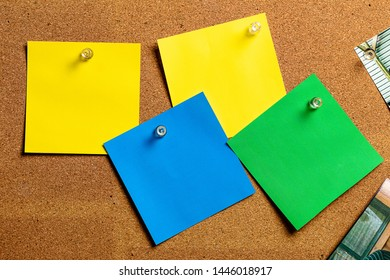 Corkboard/Bulletin Board and blank Sticky Notes in Yellow, Green and Blue, arranged in a very haphazard and natural manner making it Great for copywriting.