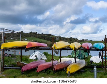 Cork/Ireland. May 2, 2019: Canoes on a rack on the foreshore with a castle tower in the background.