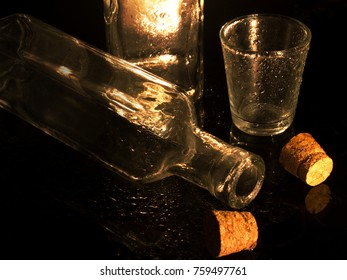 Corks, glass of water, bottle of water on black floor.