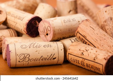 """Corks on wood. """" Mis en Bouteille"""" (which means """"filled in the bottle or bottled""""), the Origin of the Wine and or the Vintage is printed on them. Cote de Beaunes Villages is a french Region for Wine."""