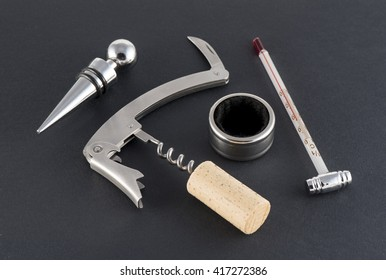 Corkscrew and accessories for wine on black background