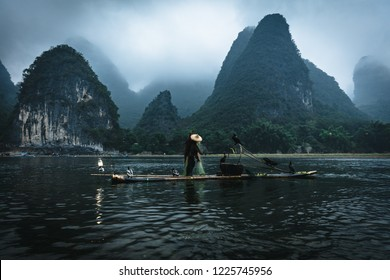 A cormorant fisherman standing on a small raft fishing in traditional chinese way with cormorant birds throwing an old fisher net into the river infront of a scenic mountain view with clouds