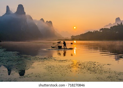 Cormorant fisherman stands on the ancient bamboo boat with cormorant birds in the sunrise - The Li River, Xingping, China