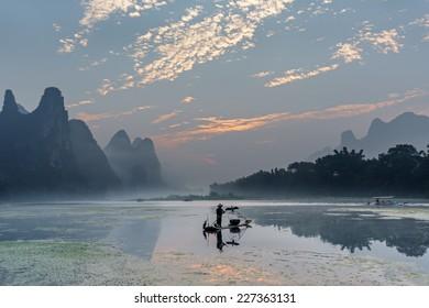 Cormorant fisherman stands on traditional bamboo boats at sunrise - The Li River, Xingping, China