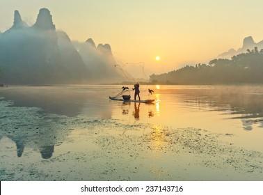 Cormorant fisherman throws a net with ancient bamboo boats at sunrise - Xingping, China