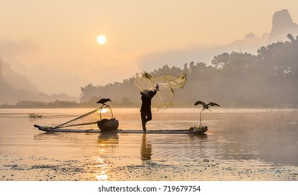 Cormorant fisherman throws a net with ancient traditional chinese bamboo boats at sunrise - Xingping, China