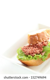 corn beef and lettuce baguette on white dish