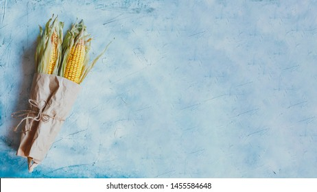 Corn bouquet on bright blue background. Bouquet made with partially shucked sweet corns with cobs. Raw sweet corns beautifully formed