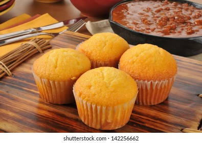 Corn bread muffins with a cast iron skillet of chili con carne in the background