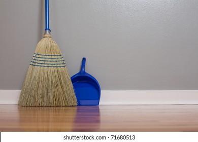A Corn Broom on New Hardwood Flooring with a dust pan