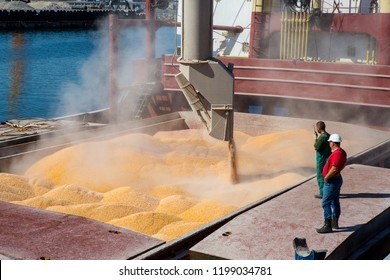 Corn in bulk carrier hold. Casting hold of corn. Elevator crane loads ship bulk carrier with corn