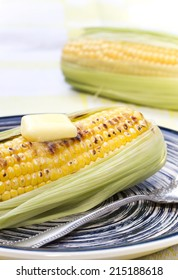 Corn with butter on a plate.