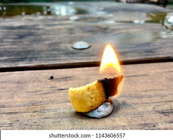 A corn chip burns with a small flame on a picnic table.