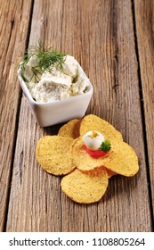 Corn chips and bowl of fresh cheese on wooden background