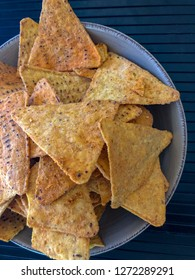 Corn chips in a bowl sitting on the table.