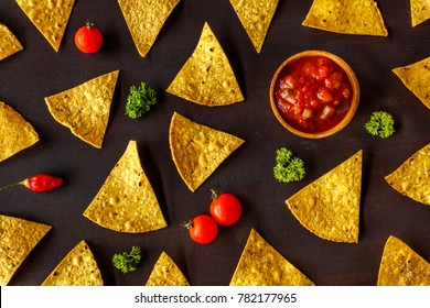 Corn chips nachos and chunky tomato salsa in a wooden bowl, cherry tomatoes, chilly pepper and parsley on a dark brown wooden surface. Square image. Top view.