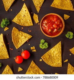 Corn chips nachos and chunky tomato salsa in a wooden bowl, cherry tomatoes and parsley on a dark brown wooden surface. Sprinkled with dry chilly pepper. Square image. Top view.