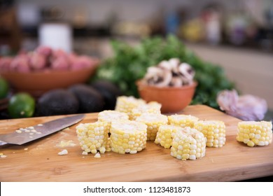 Corn cob cut into sections on cutting board with knife for soup.
