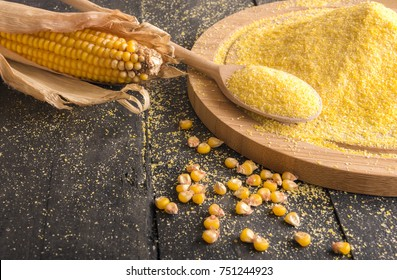 Corn cob and flour spread on table - Food ingredients theme image with a corn cob, grains and corn flour on a wooden trencher and spoon, on a rustic wooden table.