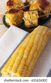 Corn cobs cooked on a grill on a wooden background. Corncobs on wooden skewers