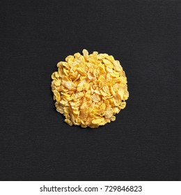 Corn flakes on black stone background, top view. Space for text