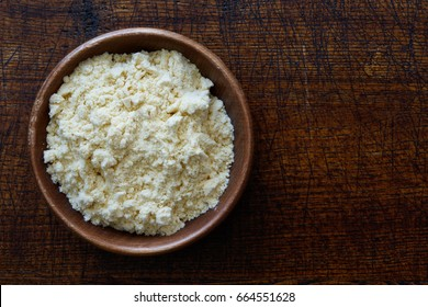 Corn flour in dark wooden bowl isolated on dark brown wood from above.