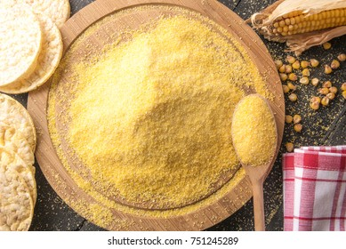 Corn flour and puffed corn cakes - High angle view image with a pile of corn flour on a round wooden board, surrounded by puffed corn cakes, on a black wooden table.