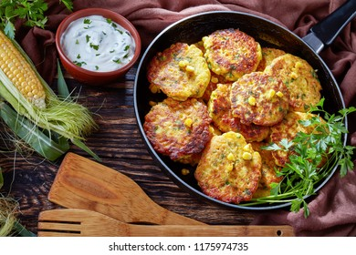corn fritters in a skillet with yogurt dipping sauce and fresh sweet corn in cob on an old rustic kitchen table, view from above