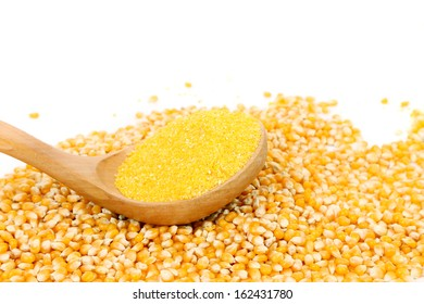 Corn grain into wooden spoon. Isolated on a white background.
