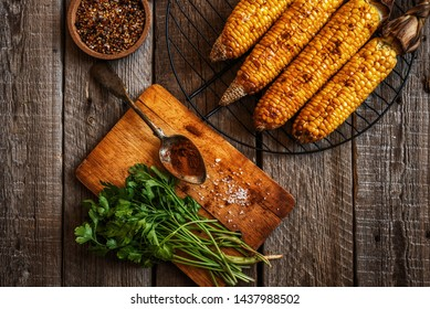 Corn grilled with cheese and spices on the dark rustic background. Autumn food background. Fast food in the summer or fall. Toned image. Flat lay.