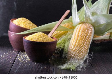 Corn grits polenta in a  ceramic bowl on white table with ripe raw corn cob and green leaves