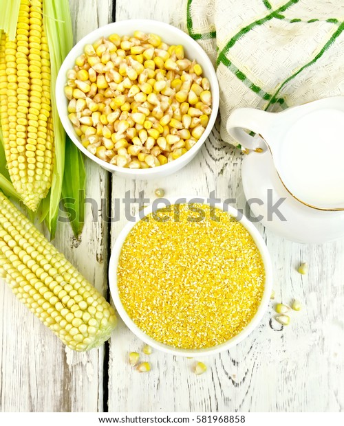 Corn grits and corn in two bowls, a napkin and cobs on the background of the wooden planks on top