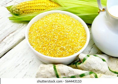 Corn grits in a white bowl, cobs, a jug of milk and a napkin on the background light wooden boards