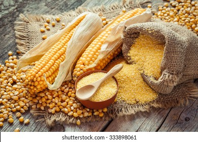 Corn groats and seeds, corncobs on wooden rustic table. Selective focus