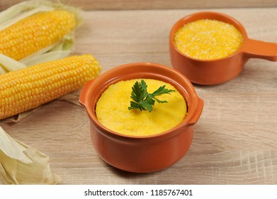 Corn hominy porridge in a clay pot. Corn flour in a clay bowl and cob of ripe corn. Light background. Close-up. View from above.