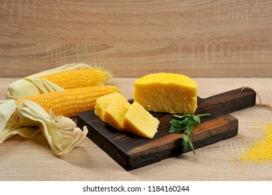 Corn hominy sliced into slices on a wooden board. Two cobs of ripe corn. Light background. Close-up.
