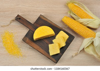 Corn hominy sliced into slices on a wooden board. Two cobs of ripe corn. Light background. Close-up. View from above.